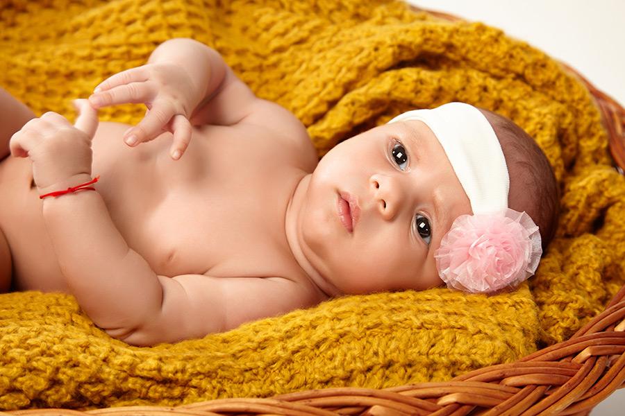 fotografie cu nou-nascut asezat in cos in studio pe fundal alb